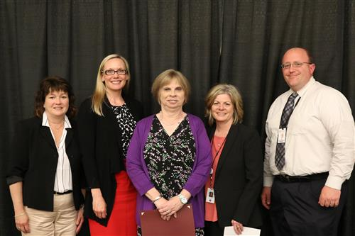 Karen Edwards (middle) posing with her certificate and NTPS Admins & Leadership.