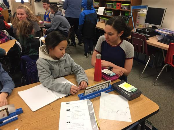 A Timberline students mentors a younger Lakes student on writing in this exchange program.