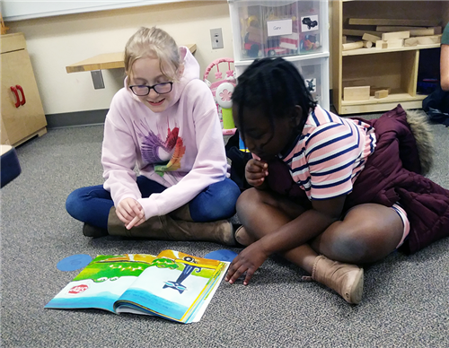 Students reading a book on the floor together