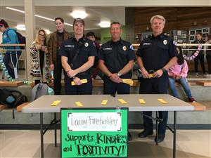 Lacey Firefighters pose in front of their kindness challenge table.