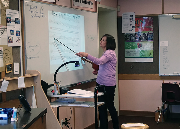 Tonni Johnston teaches the class using her violin bow as a pointer on the board.
