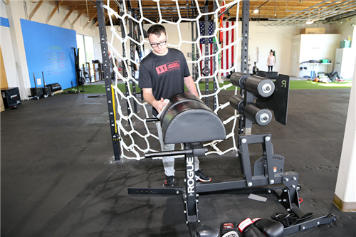 A student works to maintain equipment at a gym.