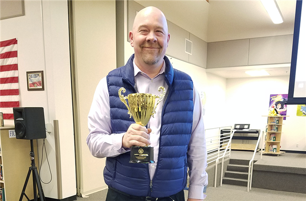 Principal Casey Crawford holds the Key Communicator cup.
