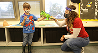 Amanda Harris plays dinosaurs with a student