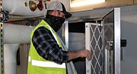 An HVAC tech installs a new filter into an HVAC system.