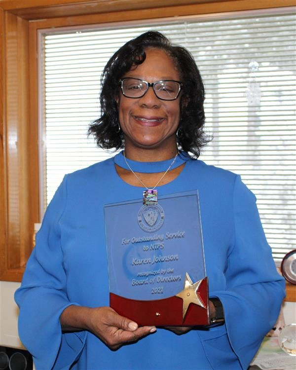 Karen Johnson holding her award from the NTPS School Board