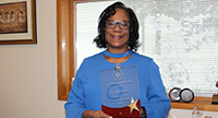 Karen Johnson holds her award from the NTPS School Board