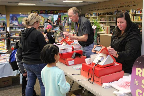 Volunteers at the Book Fair checkout counter helping shoppers.
