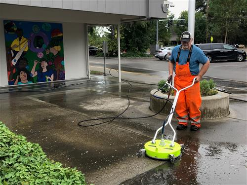 A volunteer uses the power washer on the entrance to Mountain View Elementary.