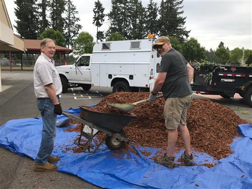 Two volunteers work on spreading bark at Lakes Elementary.