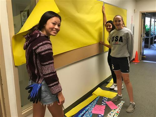 Volunteers decorate a bulletin board inside the school.