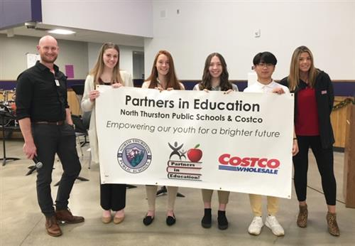 District Representatives & Costco Employees hold a banner.
