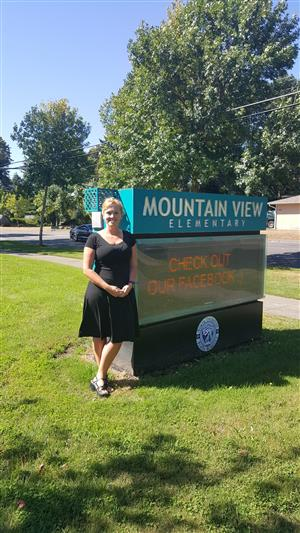 Principal McCarthy standing out in front of the Mountain View street sign.