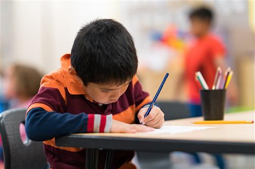 An elementary student writing on a paper while sitting at a desk.