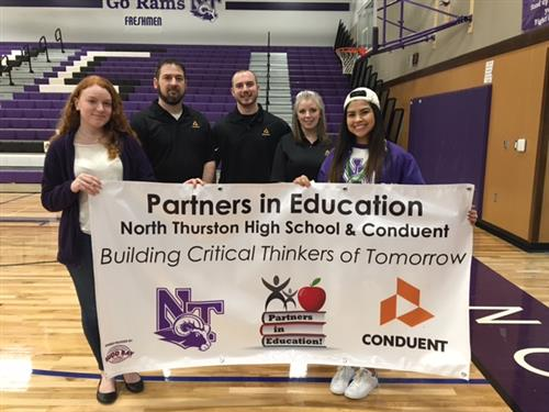Conduent and North Thurston High School hold their banner.