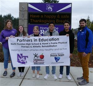 Hawks Prairie Physical Therapy staff and NTHS students hold their partnership banner.