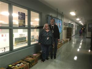 Seven Oaks staff stand in front of a hallway lind with boxes of food.