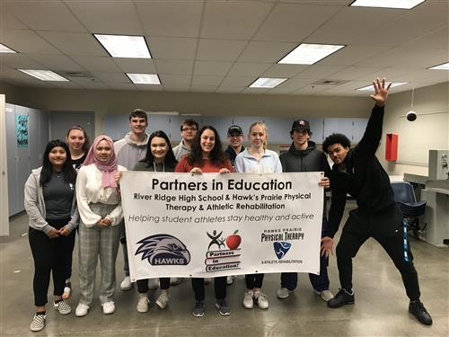 Students and employees hold a Partners in Education banner.