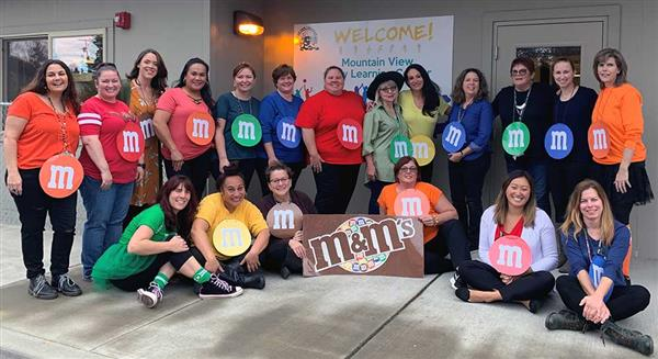 The staff standing dressing like M&M's in front of the Mountain View Preschool building.