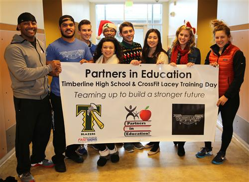 Lacey Crossfit Training Day holding a banner with Timberline students.