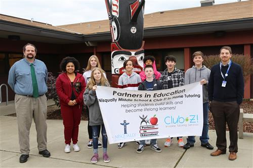 Club Z's owner, Nisqually students, and Principal Crane hold their PIE Banner.