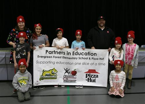 Evergreen Forest Leadership & students wearing Pizza Hut hats holding a sign with a Pizza Hut representative.