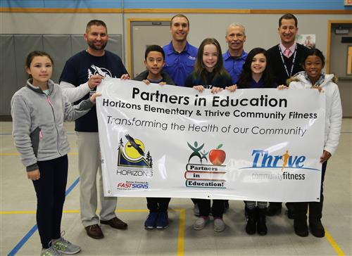 Thrive Community Fitness employees holding a banner with Horizons leadership and students.