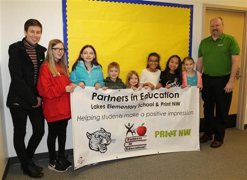 Lakes students and Print NW employees hold a banner