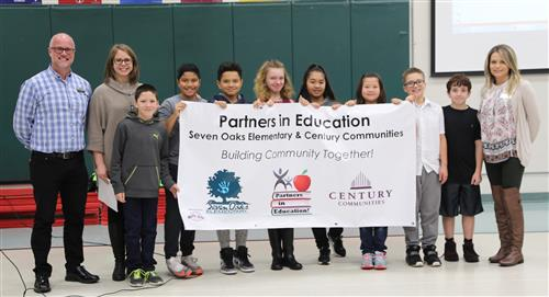 Seven Oaks students and representatives from Century Communities hold their PIE Partner banner.