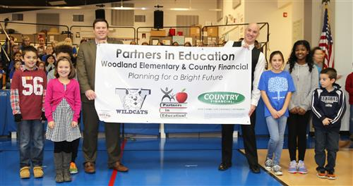 Country Financial, Woodland PIE Partner, hold our banner with students and Leadership.