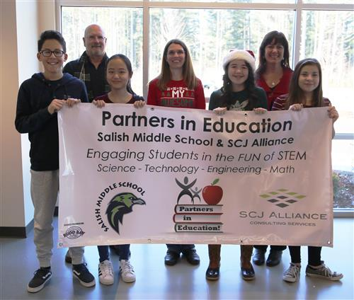 SCJ Alliance, Salish's Partner in Education, holding their banner with students & leadership